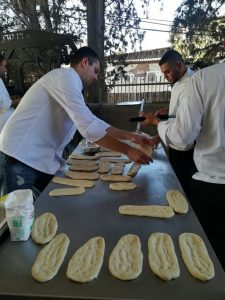 outdoor cooking שניים ממשתתפי הסדנא מגלגלים בצק לפוקצה שנכנסת לטאבון